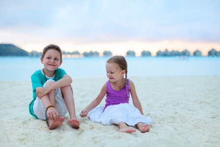Two kids at tropical vacation resort beach photo
