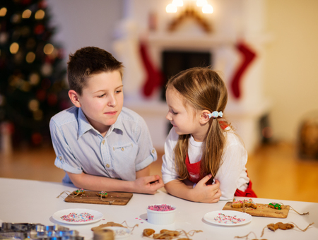 Two kids at home decorating freshly baked Christmas cookies photo
