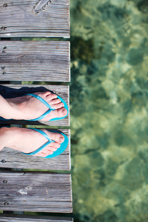 Woman legs wearing flip flops at wooden jetty by the sea photo