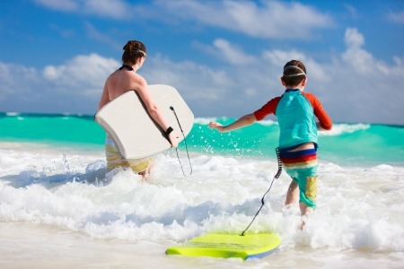 Mother and son running towards ocean with boogie boards photo