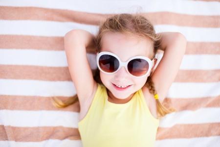 toalla: Ni�a adorable acostado en una toalla de playa durante las vacaciones de verano