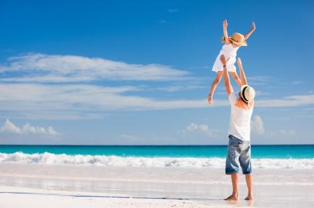 Glücklicher Vater und seine entzückende kleine Tochter am tropischen Strand Spaß Standard-Bild - 25389988