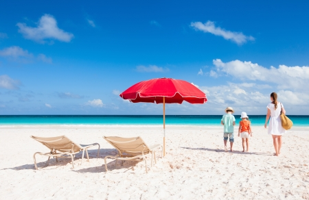 Two chairs under umbrella on a beautiful tropical beach with family walking nearby photo