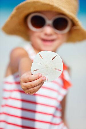 sand dollar: Ni�a que muestra d�lar de arena se encuentra en la playa