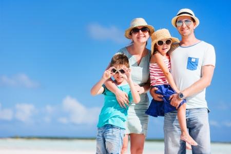 家庭: 幸福美滿的家庭在暑假期間在沙灘上擺