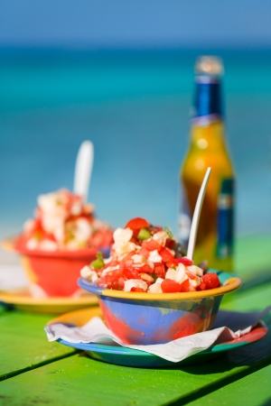 conch: Two bowls of Bahamian conch salad and bottle of beer Stock Photo