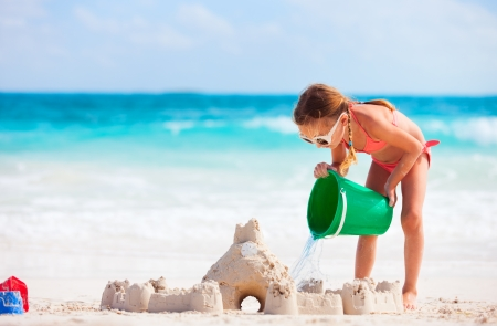 white sand beach: Little girl at tropical beach making sand castle