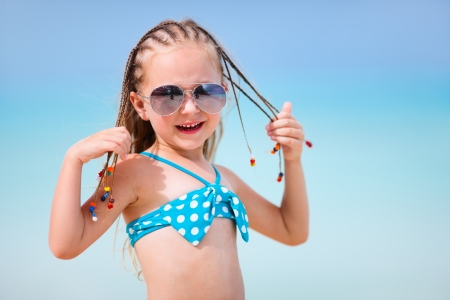 swimsuits: Adorable little girl with Caribbean braids on vacation