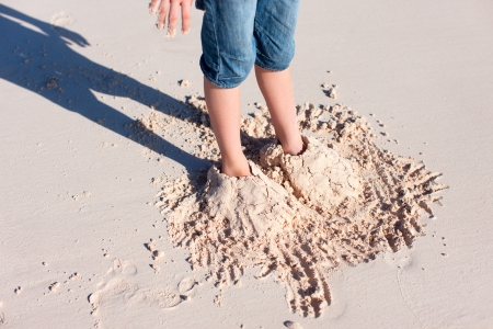 feet in sand: Little boy feet covered with tropical sand