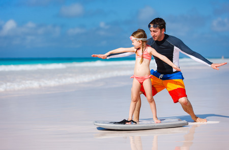 surfboard: Father and daughter at beach practicing surfing position