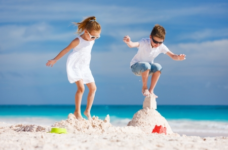 Two kids crushing sandcastle on summer vacation photo
