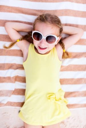 Niña adorable acostado en una toalla de playa durante las vacaciones de verano Foto de archivo - 25606965