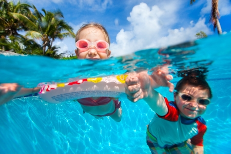 splash pool: Above and underwater photo of kids swimming in pool Stock Photo