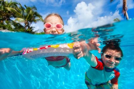 nadar: Foto de arriba y bajo el agua de los ni�os a nadar en la piscina