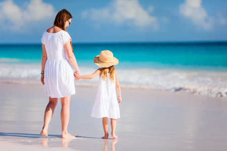 little girl beach: Back view of mother and daughter at Caribbean beach Stock Photo