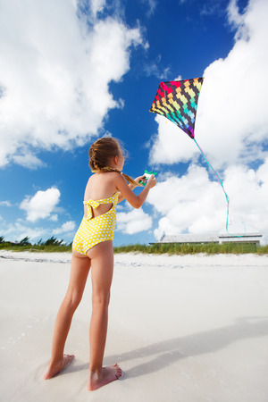 Little girl flying a kite at beach photo