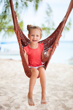 Adorable little girl swinging in hammock at beach photo