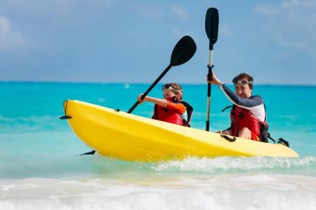 Vader en zoon kajakken in tropische oceaan Stockfoto