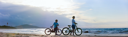 Panorama of mother and son biking on a beach at sunset Фото со стока