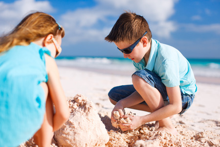 sandcastle: Brother and sister building sand castle at tropical beach Stock Photo