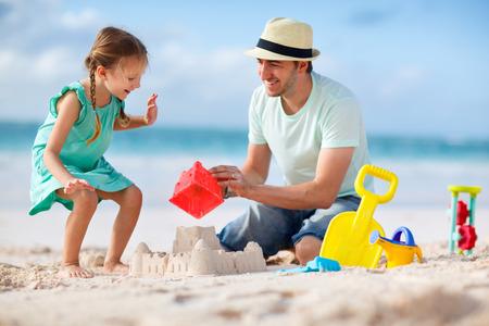 father and daughter: Padre e hija en el castillo de arena edificio de la playa