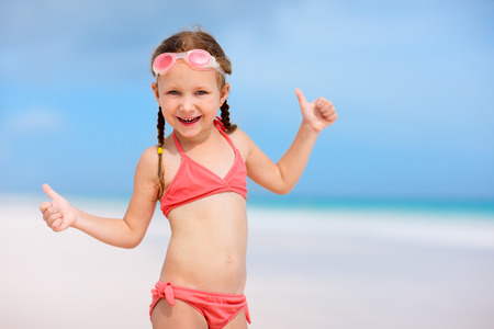 Adorable little girl at beach during summer vacation photo