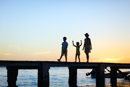 unrecognizable people: Family silhouettes on a bridge at sunset