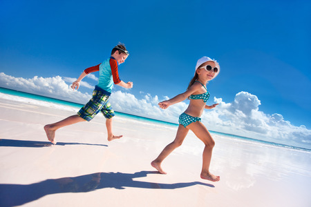 Happy kids running and jumping at beach photo