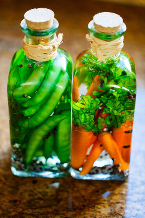 canned peas: Two clear glass jars of colorful preserved vegetables