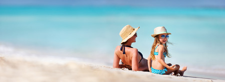 little girl swimsuit: Mother and daughter enjoying time at tropical beach Stock Photo