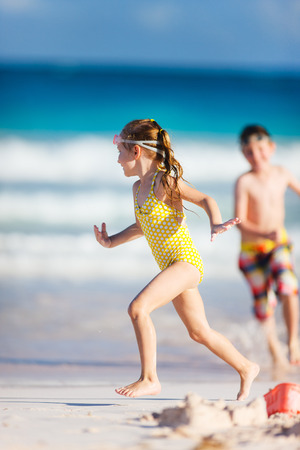 Two kids playing at tropical beach during summer vacation photo