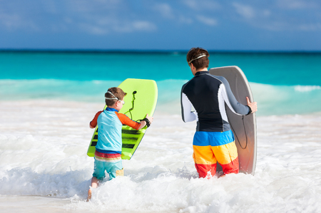 Father and son running towards ocean with boogie boards photo