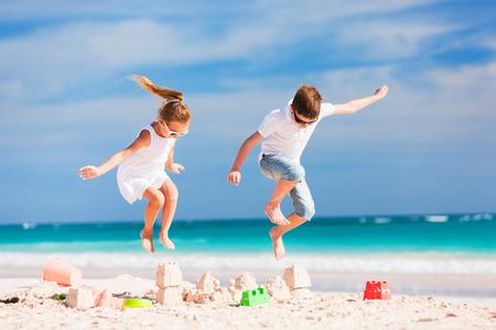 Twee kinderen verpletterende zandkasteel op zomervakantie Stockfoto