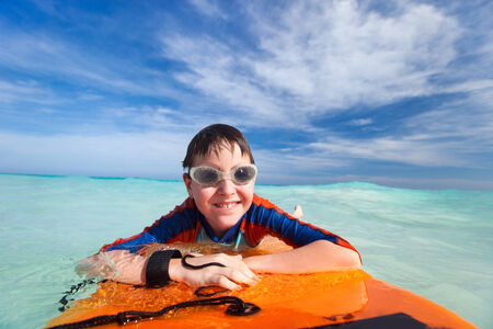 Little boy on vacation having fun swimming on boogie board photo