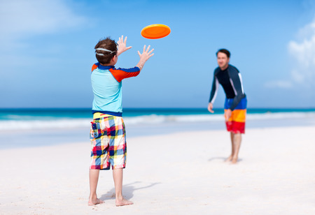 Father and son playing frisbee at beach photo