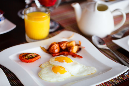 mealtime: Delicious breakfast with fried eggs, vegetables, orange juice and coffee