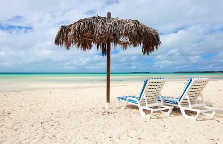 Chairs and umbrella on a beautiful Caribbean beach on Bahamas photo