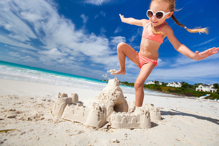 Little girl at tropical beach crushing a sand castle having fun  Stock Photo