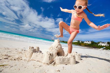 Little girl at tropical beach crushing a sand castle having fun  photo
