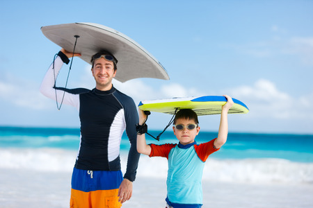 Father and son with surfboards at beach photo