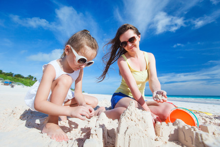Young mother and her little daughter at tropical beach making sandcastle photo