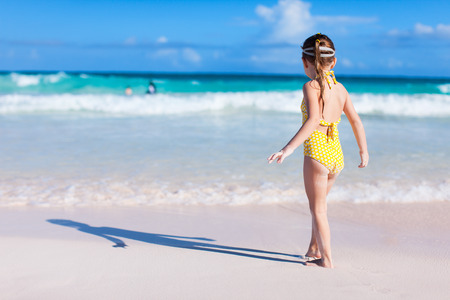 Back view of a little girl at beach during summer vacation photo