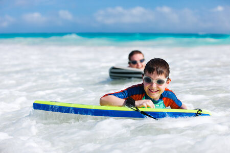 Mother and son surfing on boogie boards photo