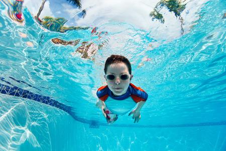 Portrait of a cute little boy swimming underwater photo