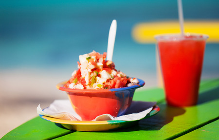 bahamian: Bowl of Bahamian conch salad and a fruit drink Stock Photo