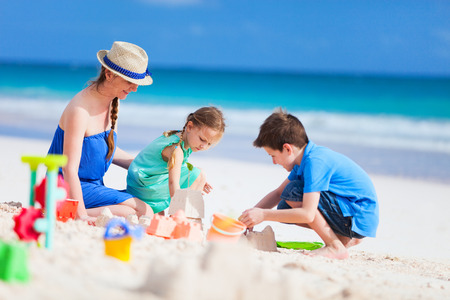Mother and kids making sand castle at tropical beach photo