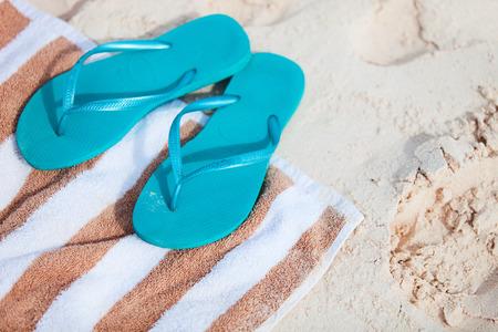 beach towel: Blue flip flops at tropical beach