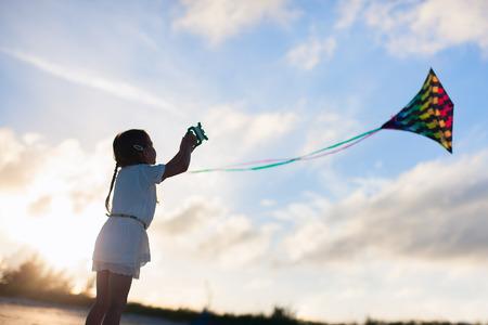 Klein meisje vliegeren op het strand bij zonsondergang