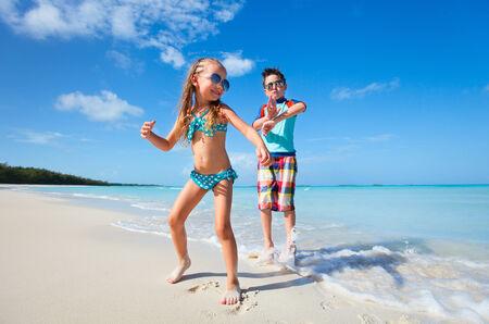 Happy kids jumping and dancing at beach Stock Photo