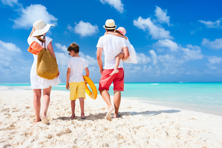 Vue arrière d'une famille heureuse sur la plage tropicale